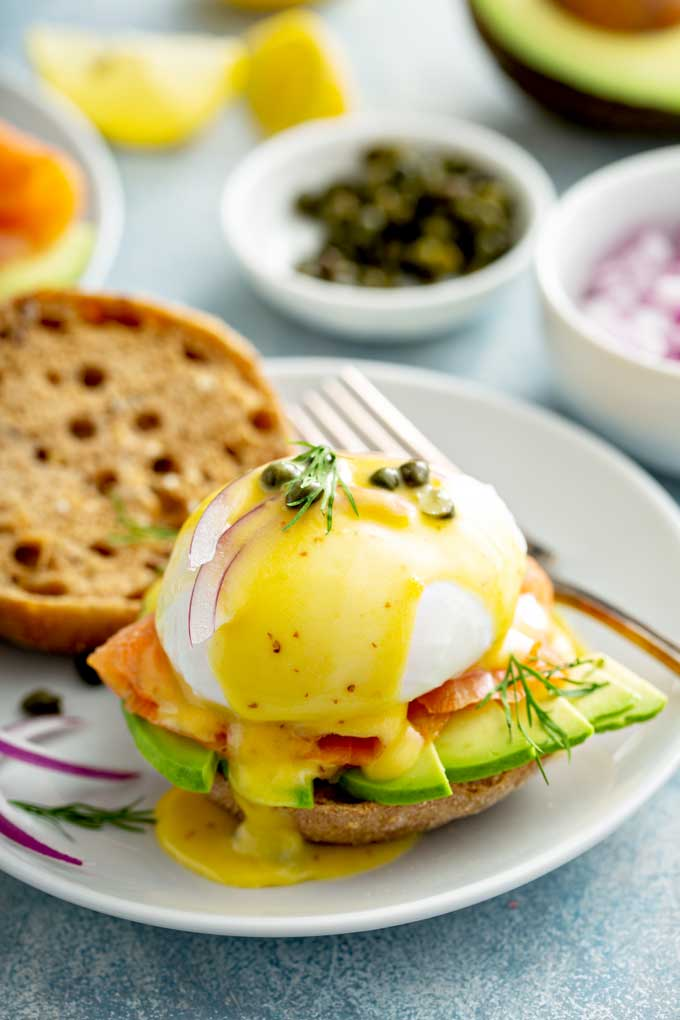 Smoked salmon topped with poached egg and Hollandaise sauce on an English muffin with sliced avocado, onions and capers