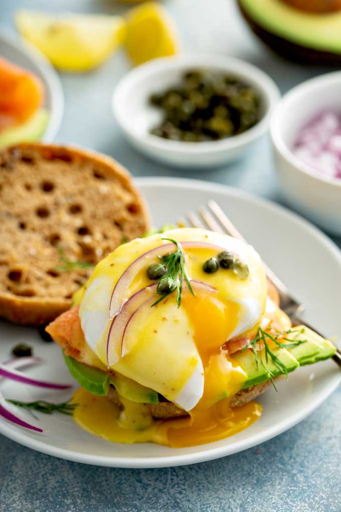 Poached egg with a runny yolk with smoked salmon, avocado and Hollandaise sauce on English muffin's toast.
