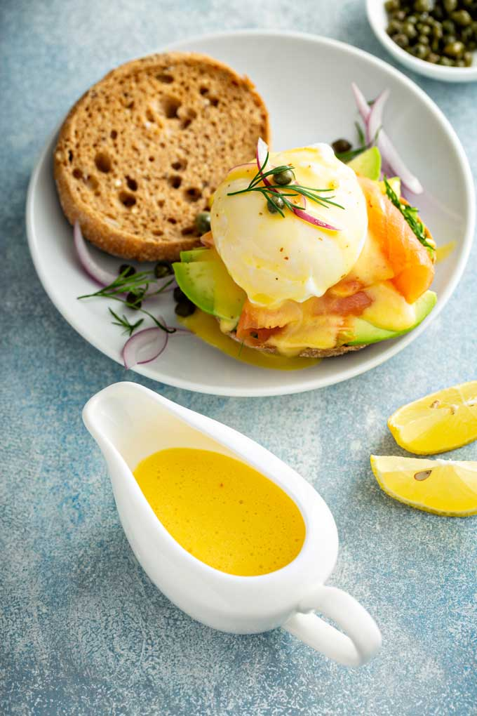 Hollandaise sauce in a white saucer next to a plate with Eggs Benedict.