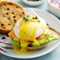 Smoked Salmon eggs Benedict with sliced avocado on a white plate
