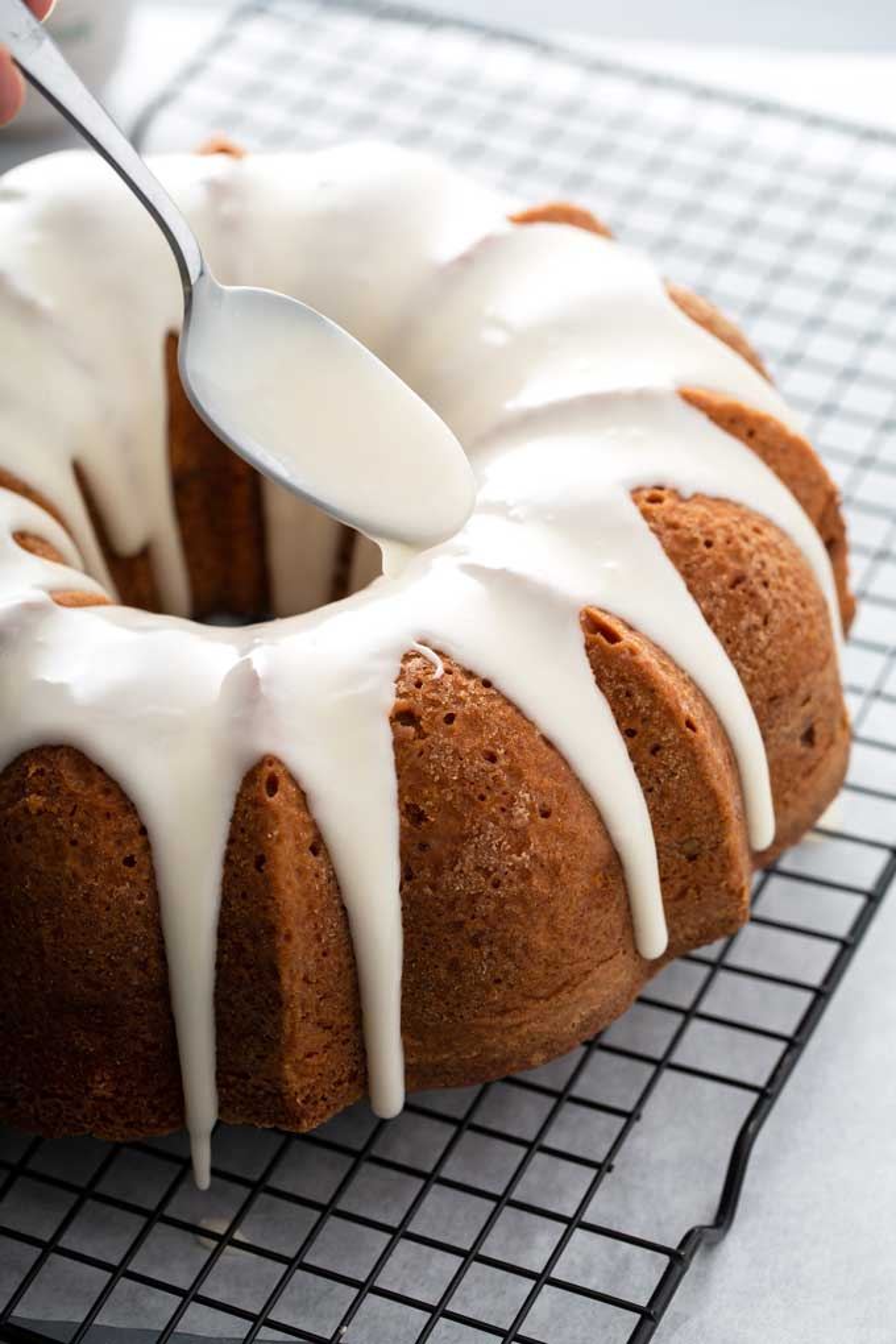 A spoon pouring vanilla glaze over bundt cake