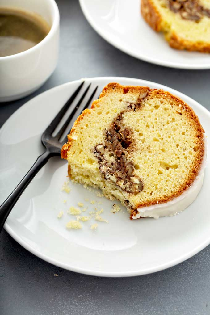 A serving of sock it to me cake showing the streusel filling on a white plate