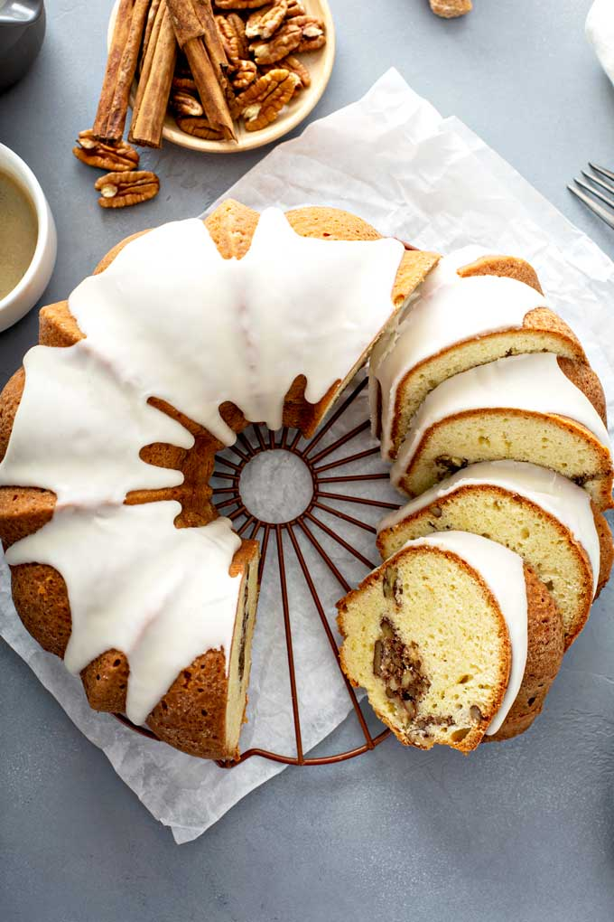 Partially sliced glazed bundt cake with a ribbon of brown sugar, pecans and cinnamon through the middle.