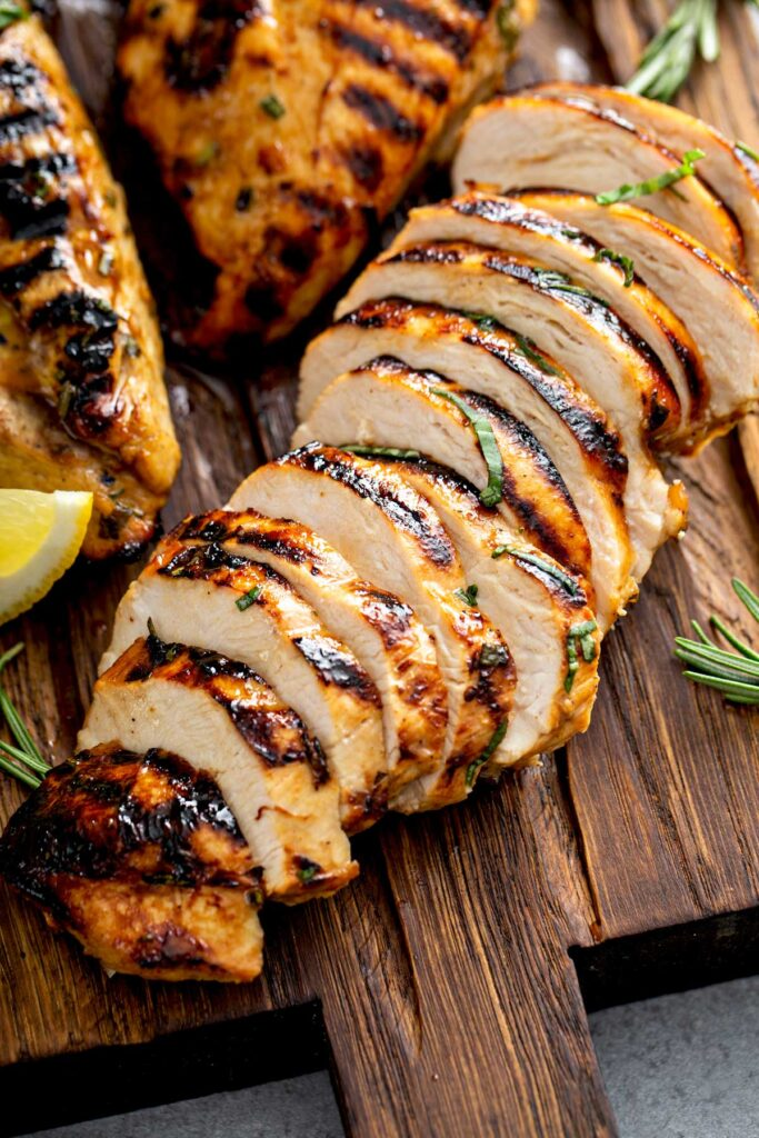 Sliced balsamic marinated chicken breast on a wooden cutting board