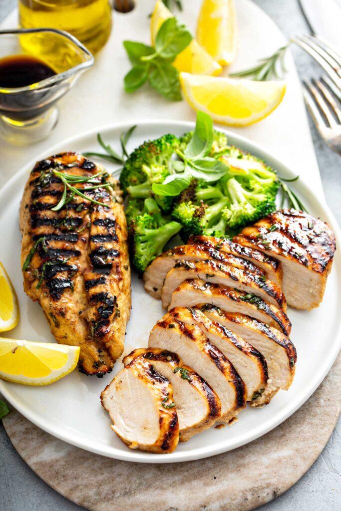 Grilled Chicken Breast - Lemon Blossoms: Sliced grilled chicken breast on a white plate served with broccoli.