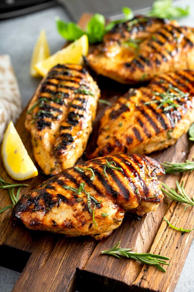 Grilled Chicken Breast - Lemon Blossoms: Grilled chicken breasts whole on a wooden cutting board