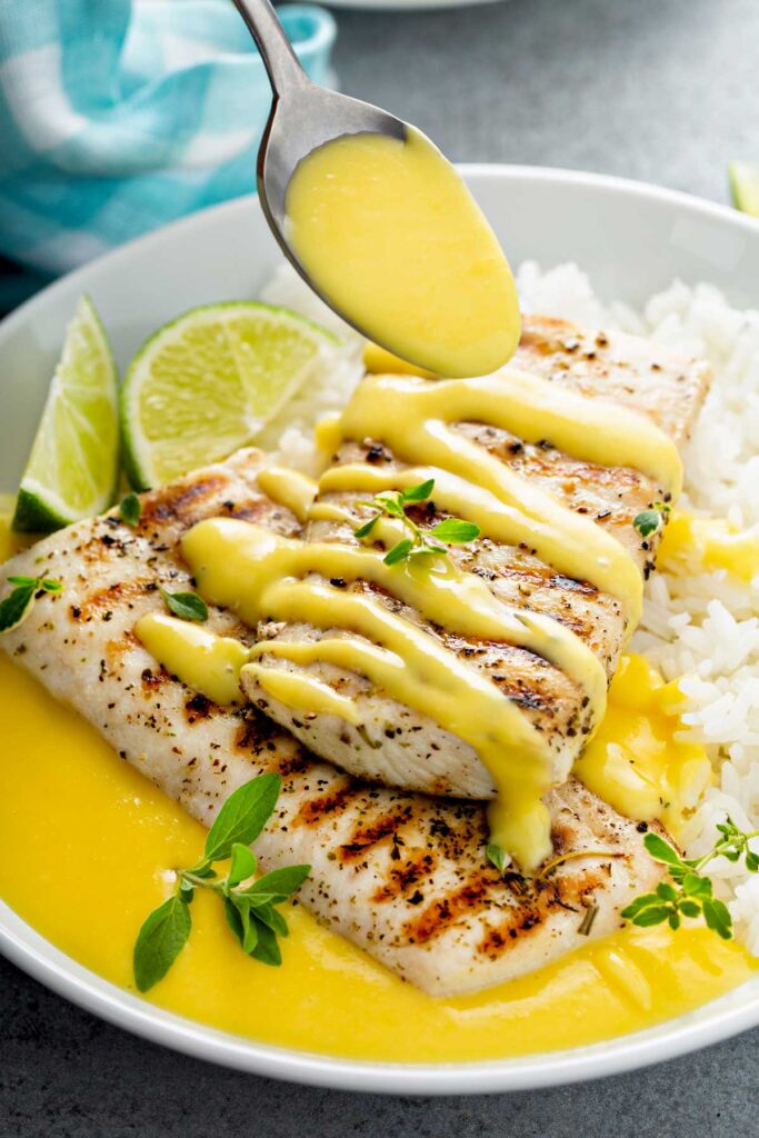 Mango lime wine butter sauce poured over grilled mahi mahi served with rice