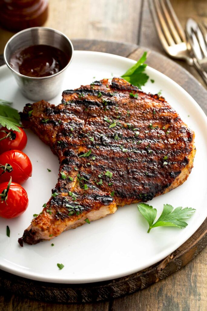 Pork chop from the grill on a white plate served with tomatoes.
