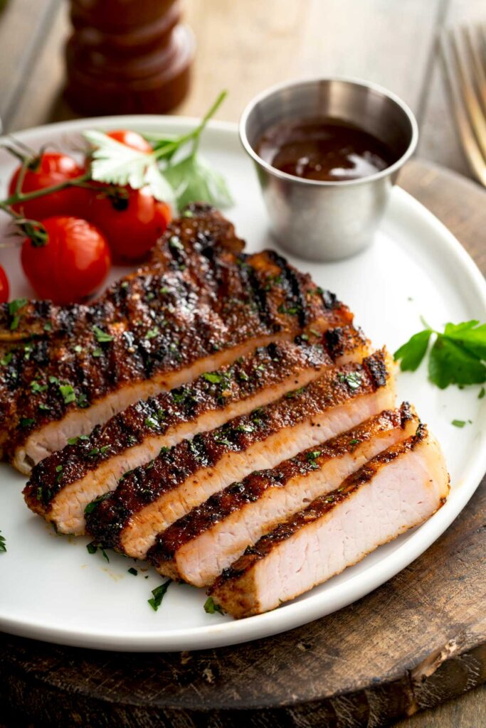 Tender and juicy sliced pork chops on a white plate.