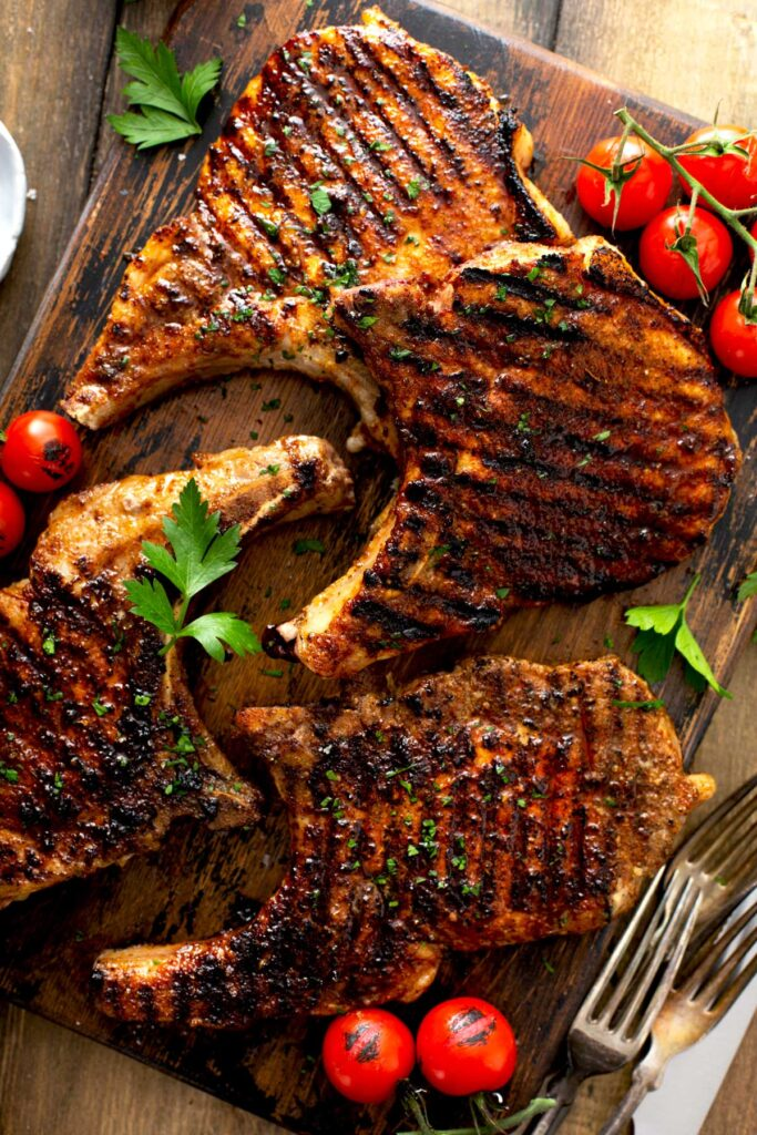 Four golden brown grilled pork chops on a wooden board