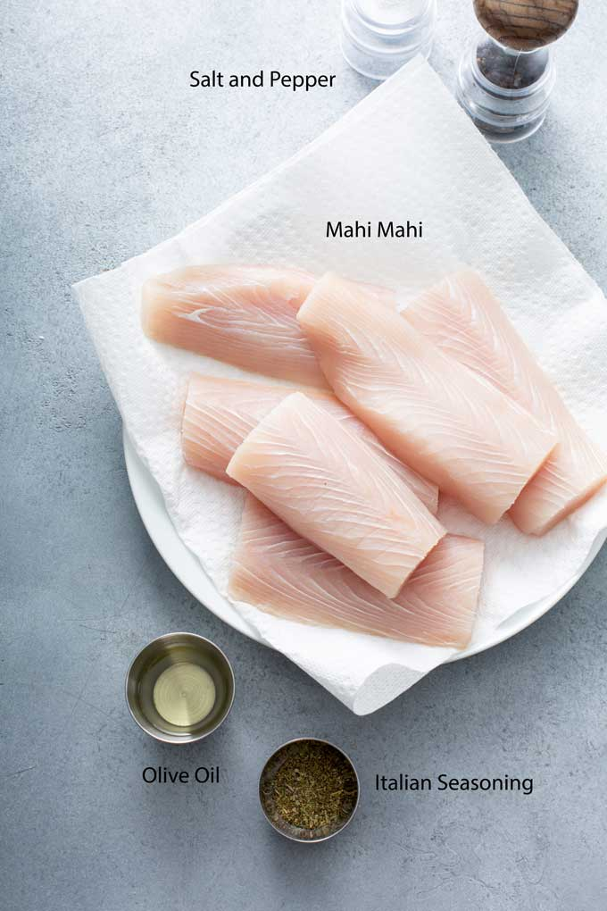 Fish fillets, olive oil and seasonings on a gray surface.