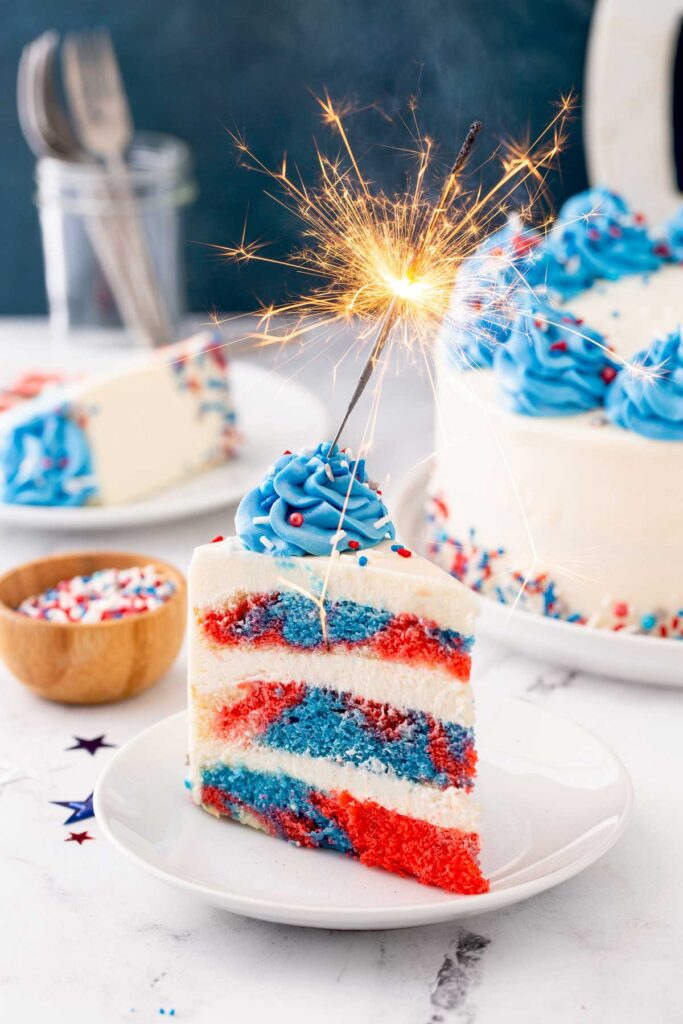 Slice of tie dye red white and blue frosted cake with a sparkler on top