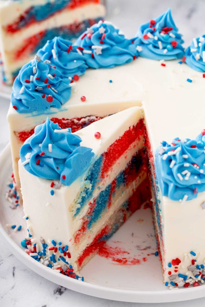 A slice of red white and blue cake cake getting taken from a whole cake