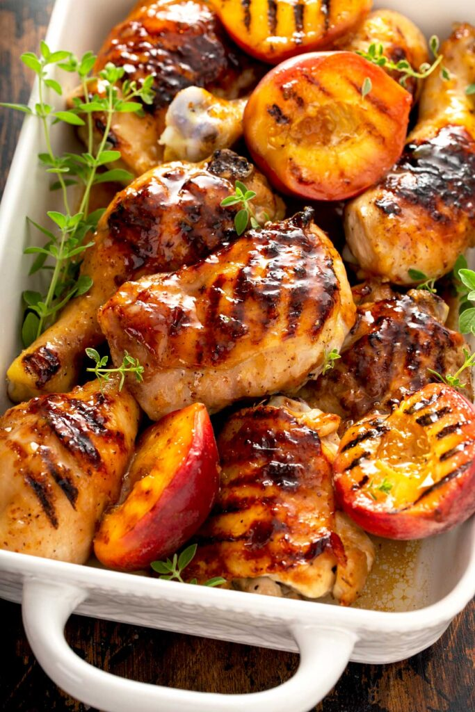 Juicy and sticky glazed chicken legs and thighs in a white ceramic pan