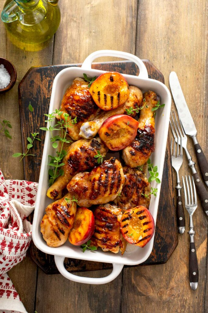 Sticky grilled chicken legs, thighs and grilled peaches in a white baking pan
