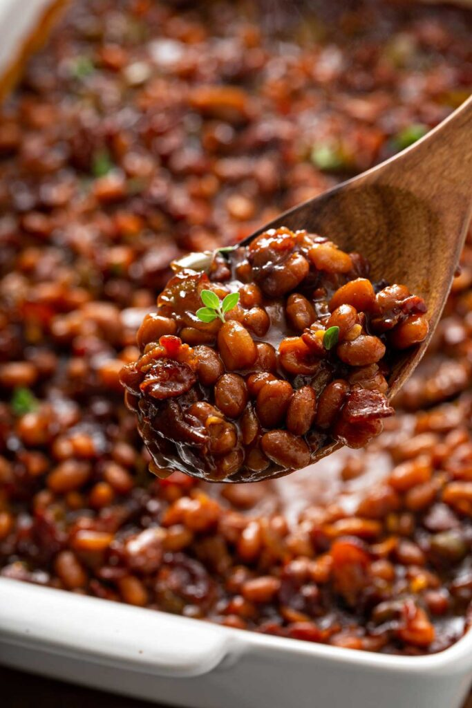 Serving baked beans with a wooden spoon from a baking dish