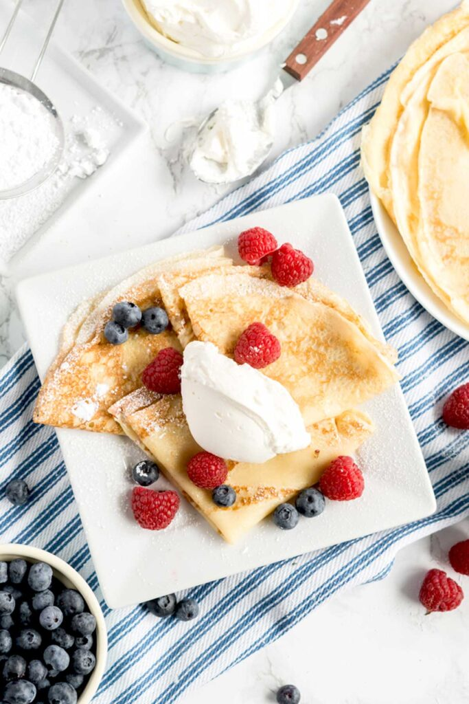 Top view of French Crepes served with sweet whipped cream and fresh berries.