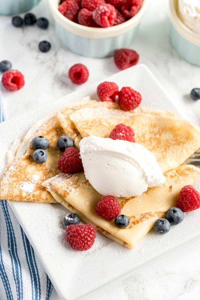 Folded homemade crepes topped with whipped cream and berries.