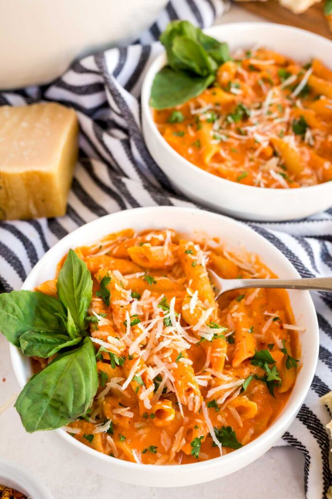 Bowls of pasta in vodka sauce topped with Parmesan cheese and fresh basil