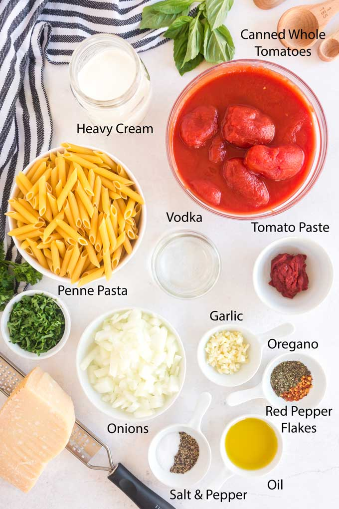 Ingredients to make penne with tomato vodka sauce on a white surface