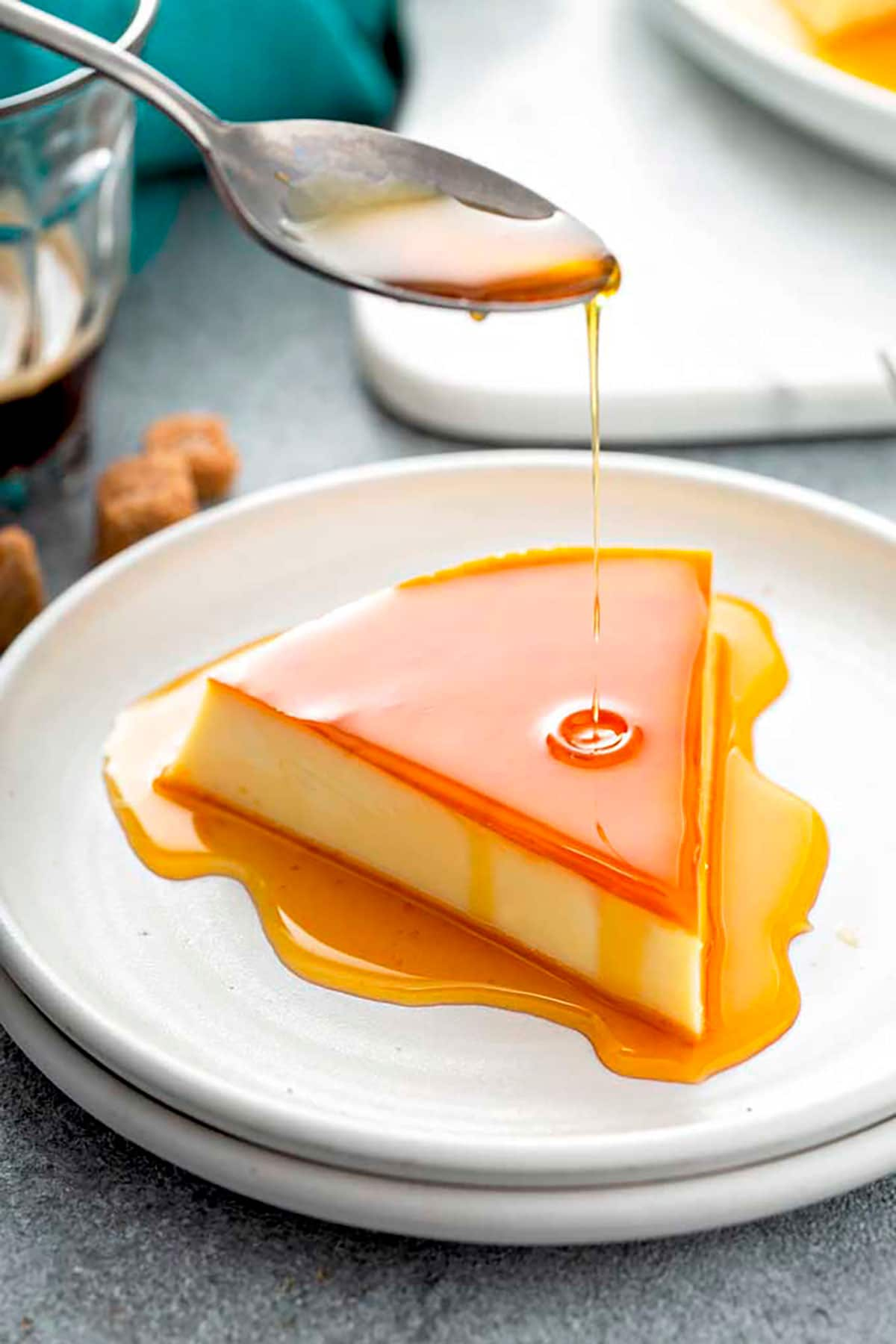 Pouring caramel over flan on a white plate.