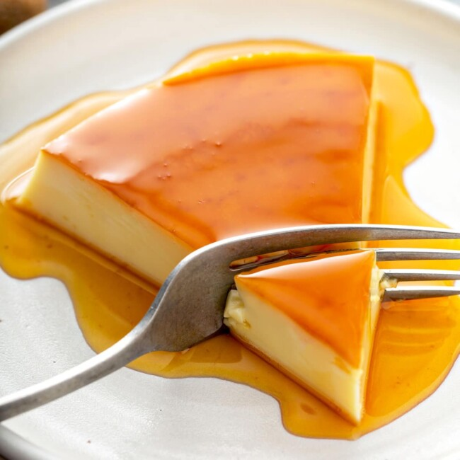 Rich and creamy flan with caramel on a white plate