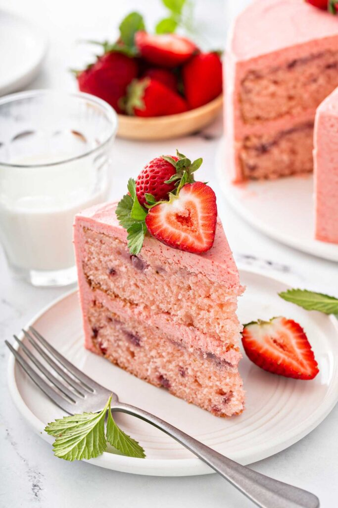 A slice of layered strawberry cake topped with fresh strawberries on a white plate