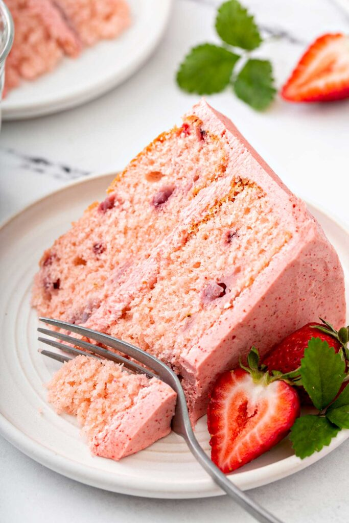 Serving of a slice of homemade strawberry cake with strawberry buttercream