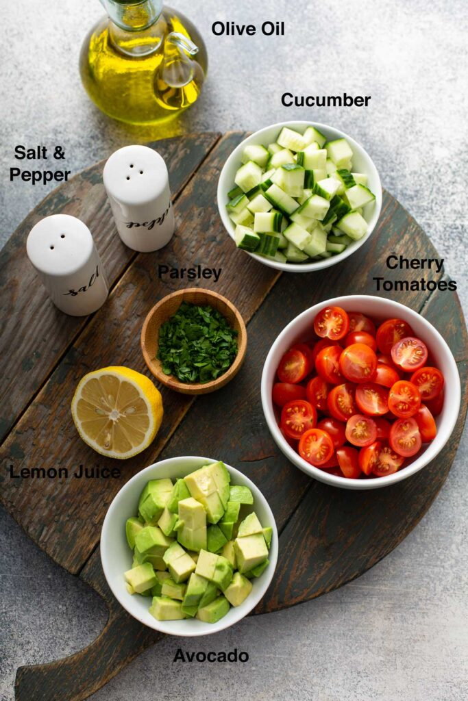 Fresh ingredients to make a chopped salad to top fish (avocado, cucumber, tomatoes)