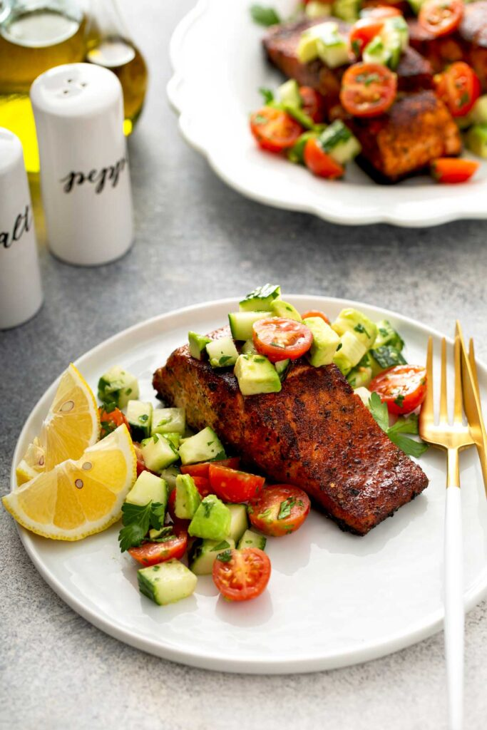 Blackened salmon recipe with a fresh cucumber tomato and avocado salad served on a white plate