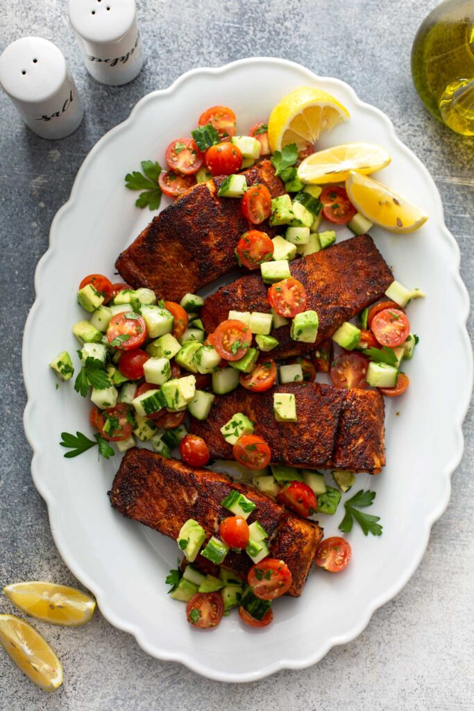 Pan seared fillets of salmon coated in blackening spices and topped with a fresh chopped salad