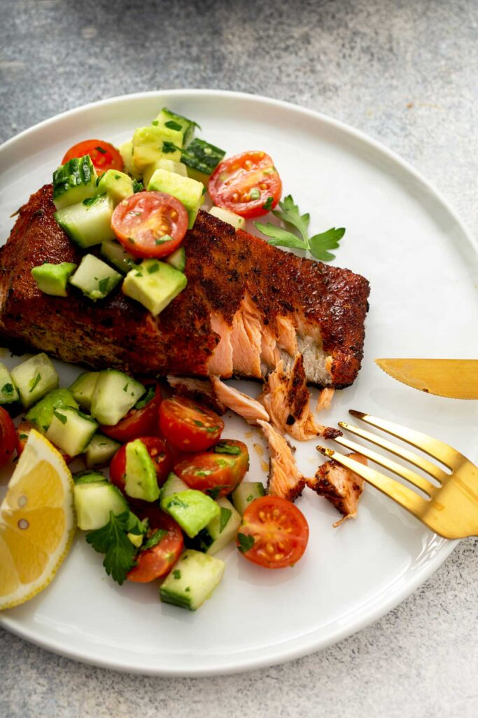 Flaky salmon fillet with blackening spices on a white plate topped with cucumber, tomatoes and avocado salad