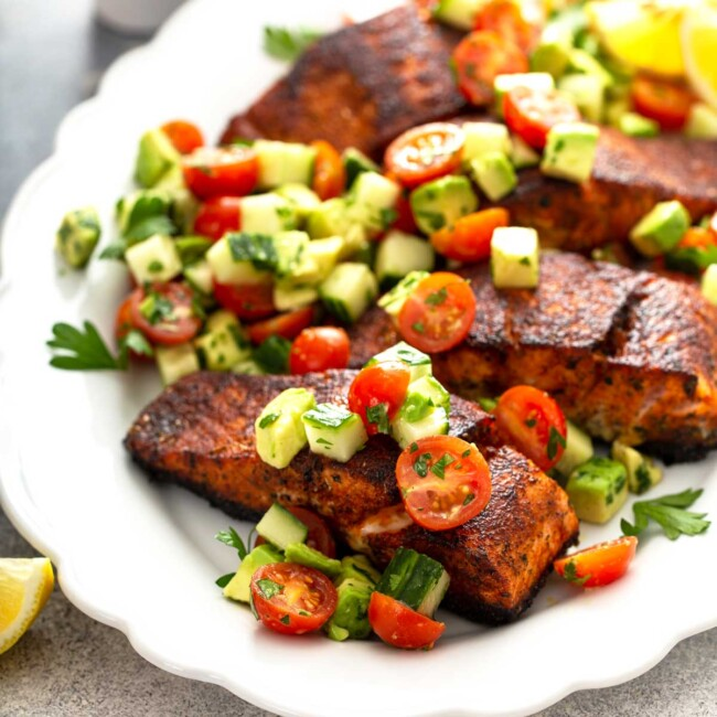 Blackened salmon recipe with chopped salad of tomatoes, avocado and cucumbers on a white platter
