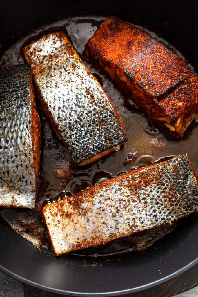 Fish fillets pan searing in a cast iron skillet.