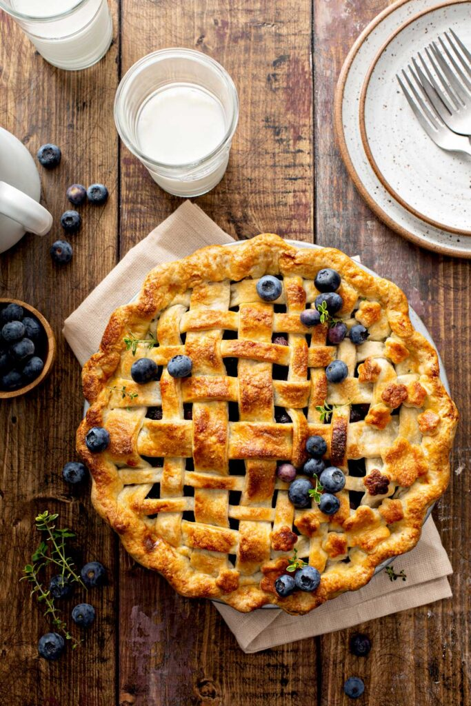 A whole blueberry pie with a lattice golden brown pie crust