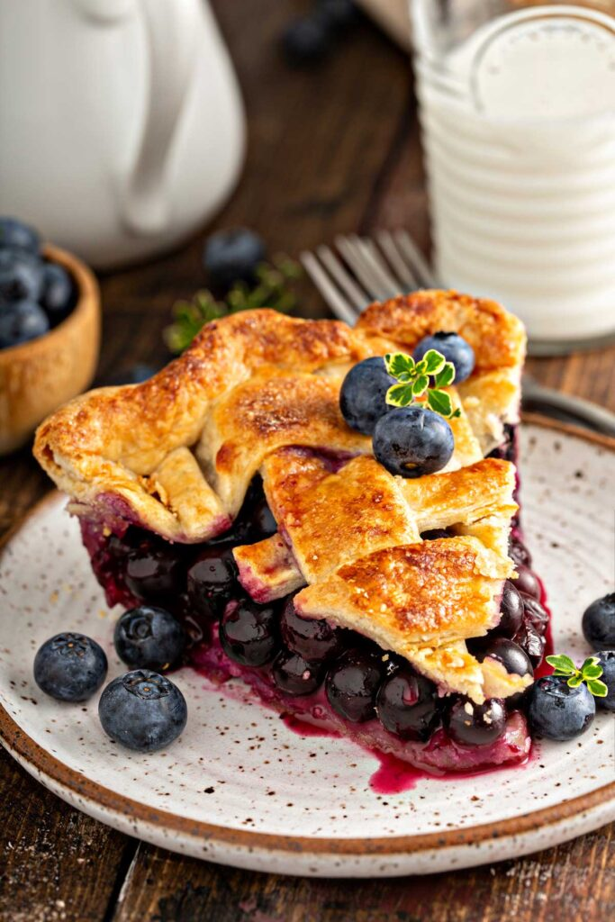 Slice of blueberry pie with golden brown and flaky pie crust on a plate