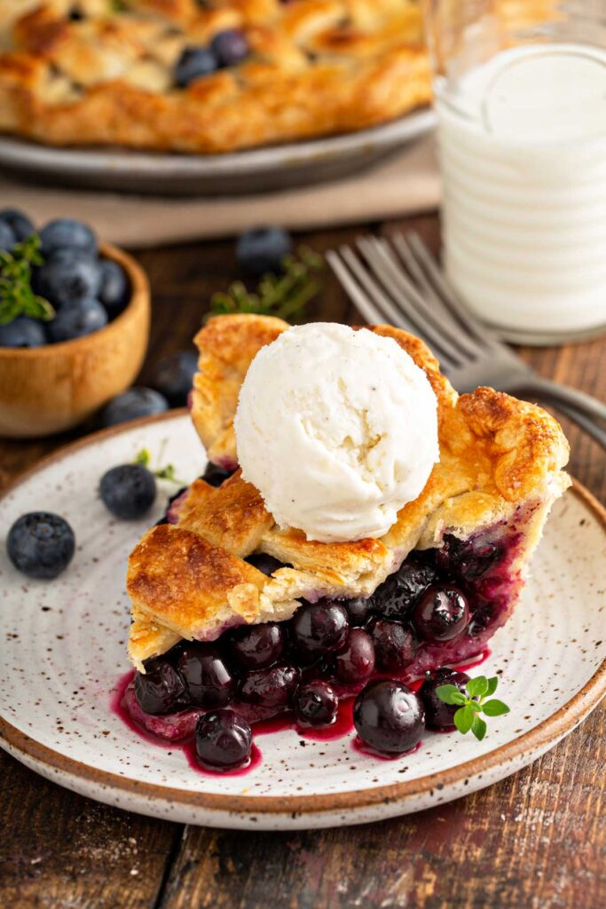 Sliced of homemade blueberry pie topped with vanilla ice cream