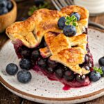 A piece of easy fresh blueberry pie with a golden brown flaky crust on a plate