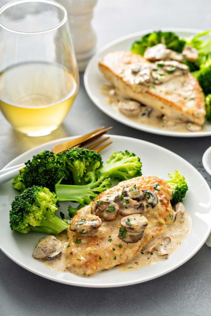 Chicken cutlet served with mushroom sauce and broccoli in a white plate
