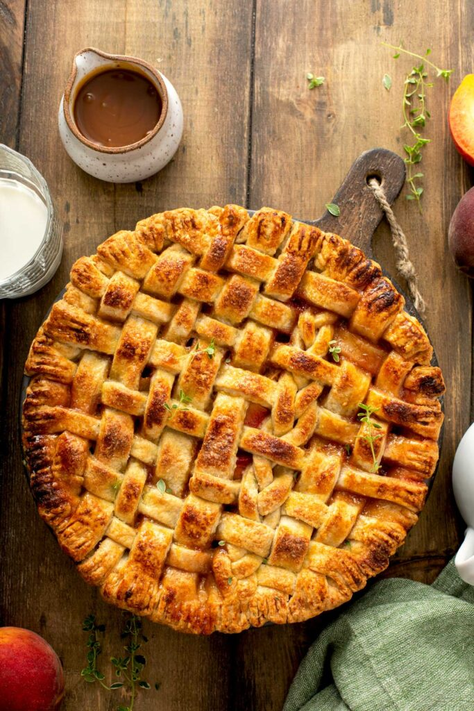 A whole peach pie with a lattice crust on a wooden table