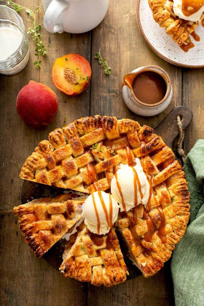 A whole peach pie topped with vanilla ice cream and drizzled with caramel sauce