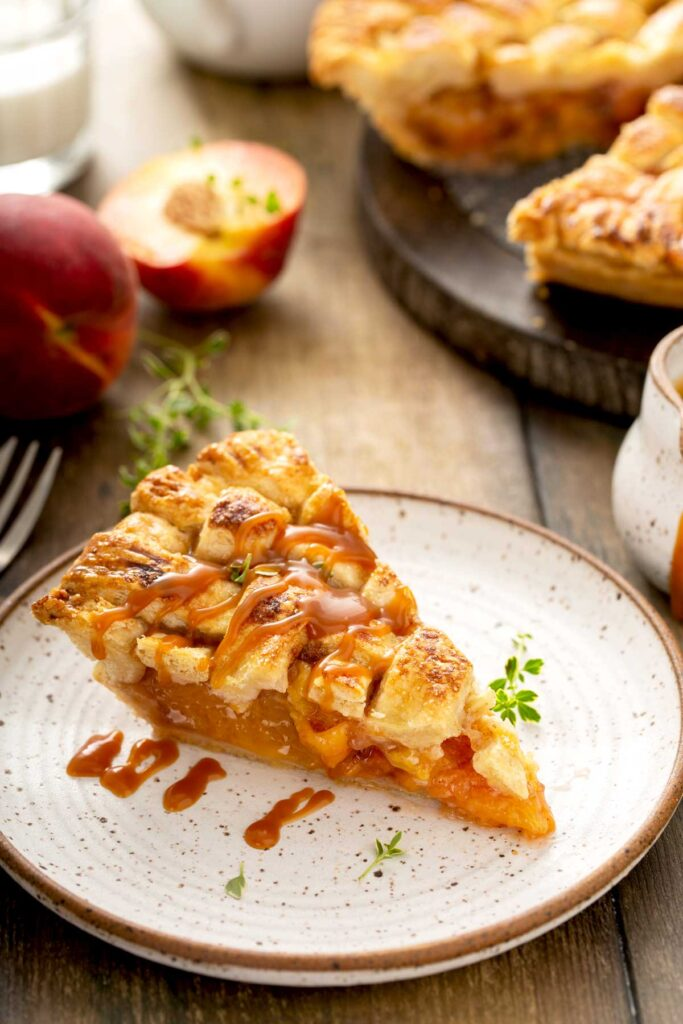 A slice of peach pie served with Bourbon caramel sauce on a white plate