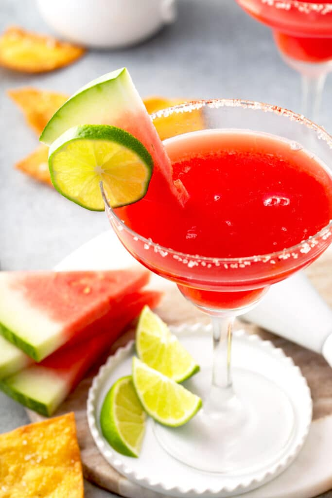 Watermelon margarita garnished with a fresh watermelon wedge and lime slices