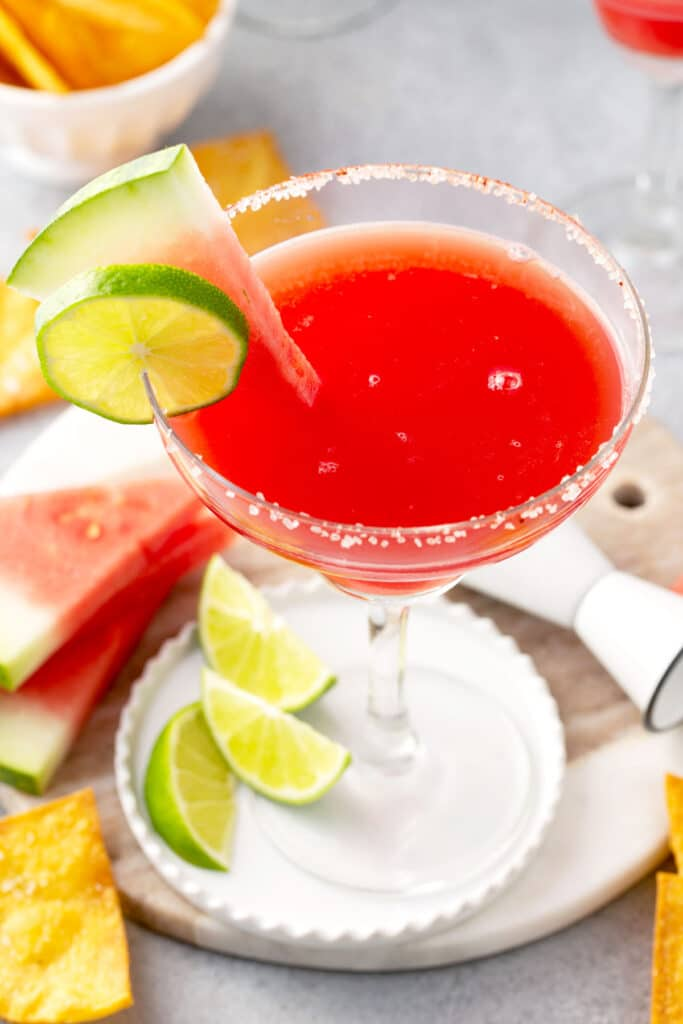Vibrant red, watermelon and tequila cocktail in a margarita glass with limes.