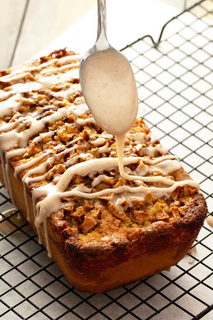 A spoon drizzling cinnamon glaze over apple loaf