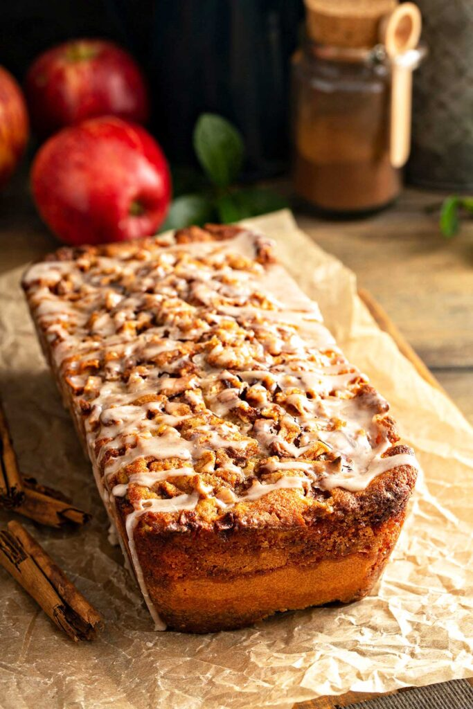 A loaf of apple bread with cinnamon sugar topping and drizzles with cinnamon glaze.