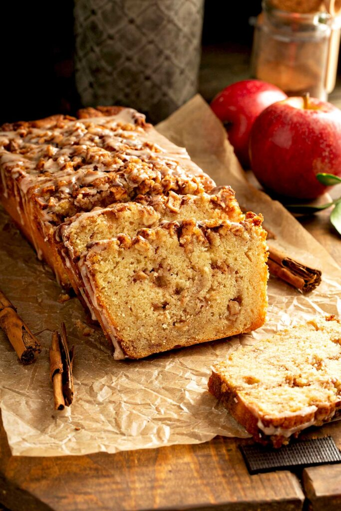 Partially sliced homemade apple quick bread with cinnamon sugar streusel and glaze