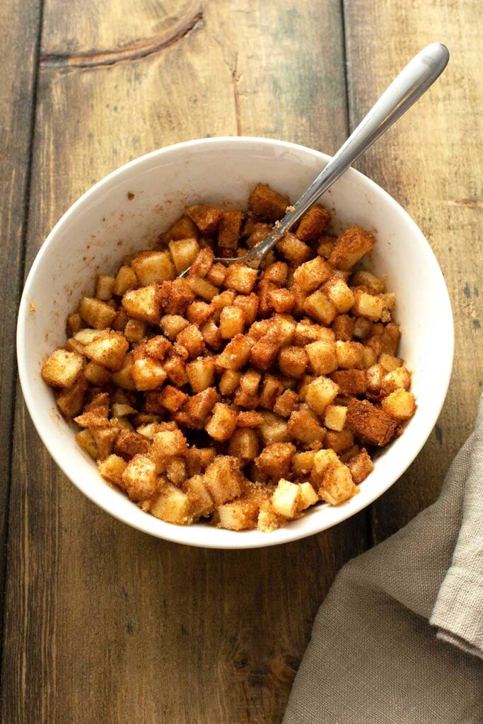 Diced apples tossed with brown sugar and cinnamon in a white bowl