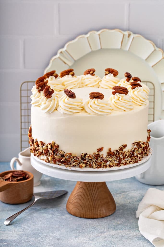 Butter Pecan cake frosted with cream cheese frosting and decorated with chopped and whole toasted pecans.