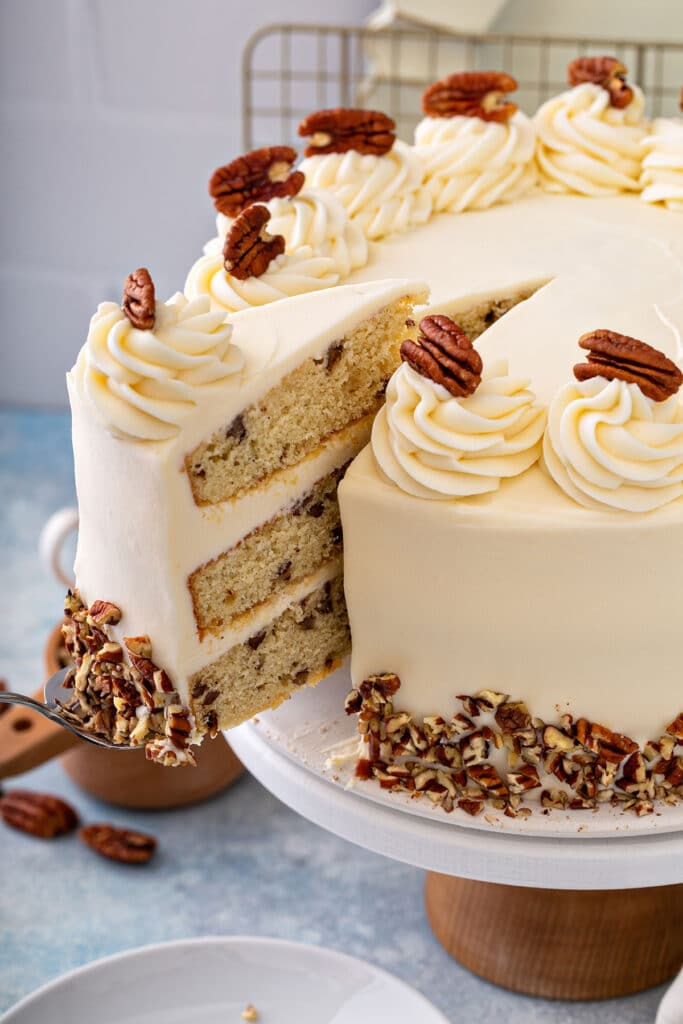 A slice of butter pecan cake getting lift from a cake platter
